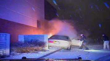 Officer pulls open the door of the burning car.
