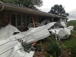 Roof torn off building slams into family's home.