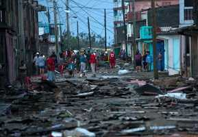 Red Cross workers and residents walk among the damage caused by Hurricane Matthew in Baracoa, Cuba, Wednesday, Oct. 5, 2016. The hurricane rolled across the sparsely populated tip of Cuba overnight, destroying dozens of homes in Cuba's easternmost city, Baracoa, and leaving hundreds of others damaged.(AP Photo/Ramon Espinosa)