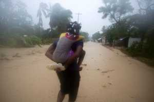 A woman carries a child through a waterlogged street as they head to a shelter under the pouring rain triggered by Hurricane Matthew in Leogane, Haiti, Tuesday, Oct. 4, 2016. Matthew slammed into Haiti's southwestern tip with howling, 145 mph winds tearing off roofs in the poor and largely rural area, uprooting trees and leaving rivers bloated and choked with debris.