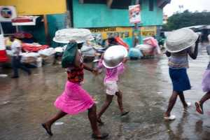 Women cover their heads with pans as they walk in a light rain brought by Hurricane Matthew in Port-au-Prince, Haiti.Women cover their heads with pans as they walk in a light rain brought by Hurricane Matthew in Port-au-Prince, Haiti.