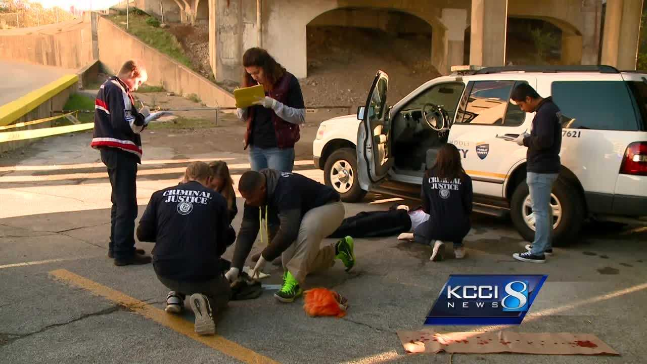 High school students study mock crime scene in forensic class