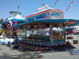 Workers are preparing the midway for Thursday's opening.