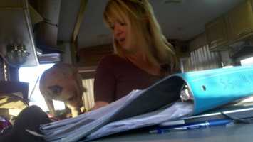 Grace Foundation director Beth DeCaprio looks through some of her legal documents and unpaid bills.