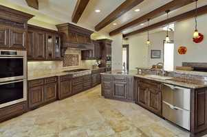 The open kitchen has granite counters, granite backsplash, a stainless steelsink, double ovens, and the list goes on.