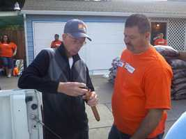 Morey speaks to one of the volunteers. The volunteers put their expertise to work in updating his bathroom, front yard and paint.