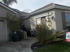 Code enforcement officials survey a home in Elk Grove on Tuesday.