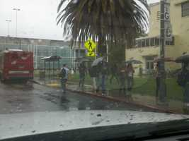 Students at UC Davis walk through rain on Thursday.
