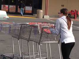 A Raley's employee in West Sacramento wheels carts back toward the store as crowds picked up after word spreads that the strike had ended.