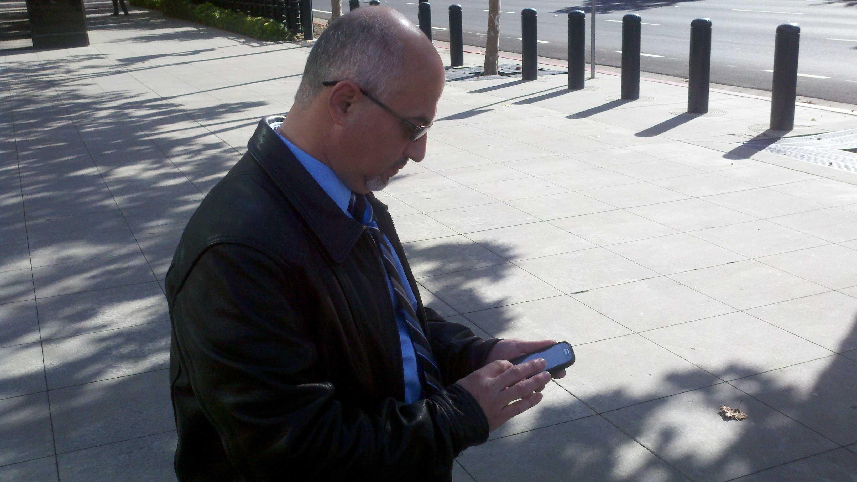 Adeeb Alzanoon checks his smartphone for the latest developments in Gaza.