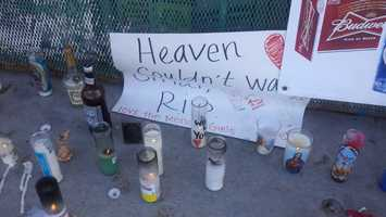 Candles are placed Tuesday outside a store on East Main Street in Stockton where a store clerk was shot and killed.