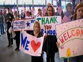 Family members and friends hold signs, welcoming him home.