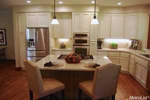 The kitchen has stainless steel appliances, custom cabinetry and a large island for eating and cooking.
