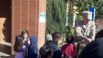 Pusley shakes hands with children outside of the school.