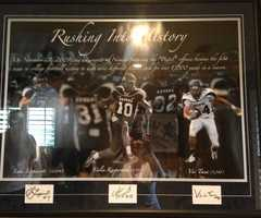 """A framed picture in Colin Kaepernick's parents' home of """"Rushing into History"""" from Colin's college football career."""