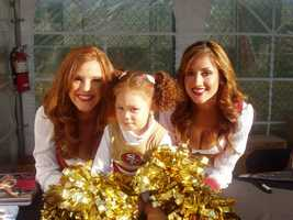 A young 49ers fans with team cheerleaders.