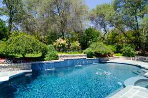 The pool and spa include waterfalls and is enclosed with wrought iron railing from Italy.