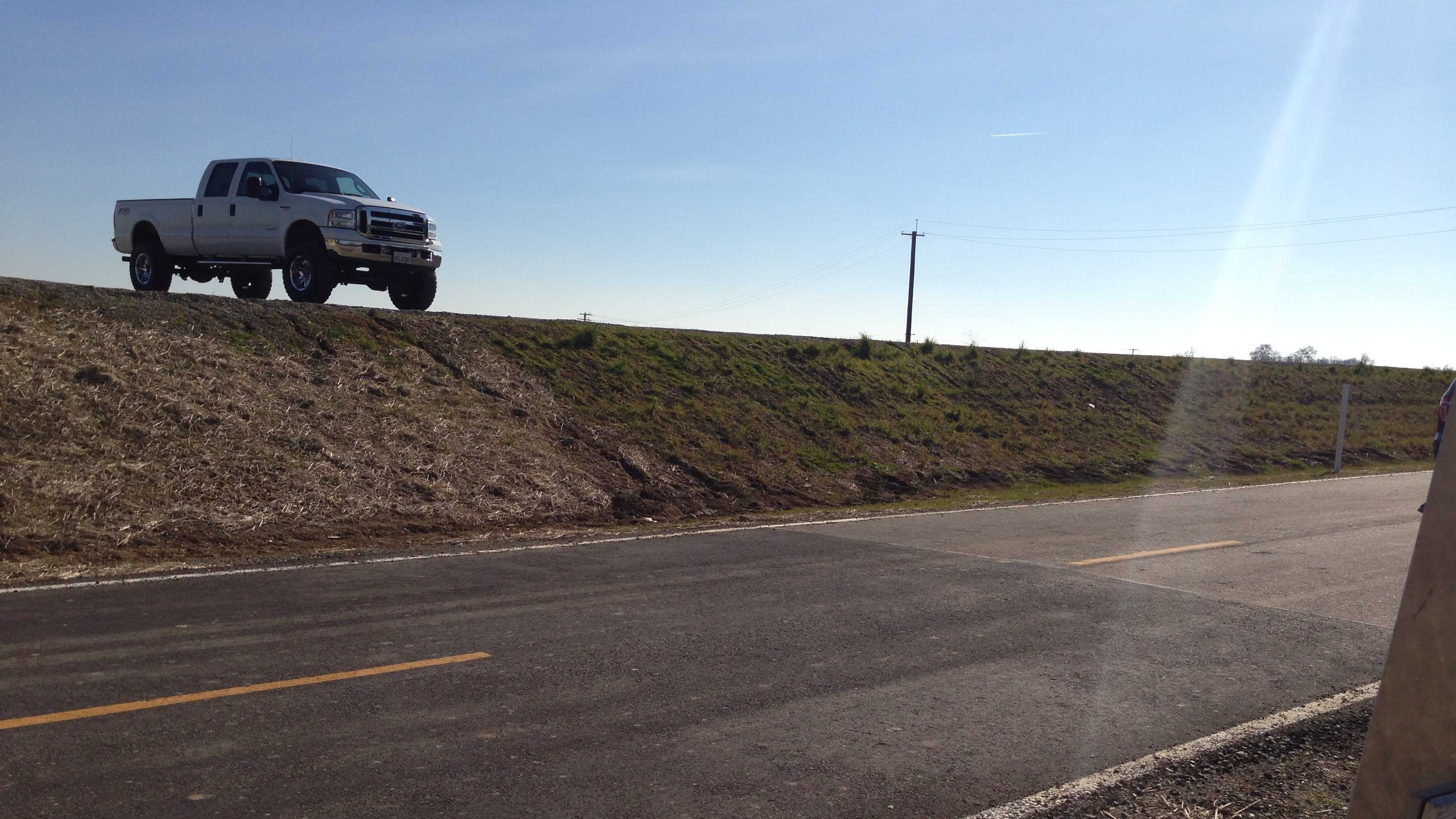 A truck sits atop the newly raised levee along the Garden Highway north of Sacramento.
