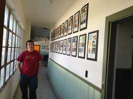 John Baccigaluppi looks at some of the album covers that line the hallway at the Hangar Studio.
