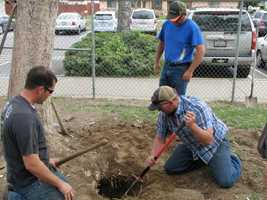Workers clear out the hole where the elementary school time capsule was buried.