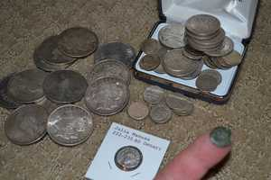 """12.) I'm a bit of a casual coin collector. It's nothing of real value, but being a history buff, I love things that can connect me to the past. A couple of things to note in this picture, the big coins are Morgan silver dollars and Peace Dollars. The one in the white card is a Roman coin dating to 255 A.D. The coin on my finger is called a """"mite,"""" given to me as a present by my mom. It relates to a Biblical tale of """"The Old Woman and the Mite."""" It's a good lesson in giving."""