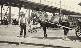 Then: A man leads a horse hitched to a wagon. In the background, is the approach to the I Street bridge, near today's Railroad Museum. Railyard shop buildings are visible in the background behind the viaduct. This photo was taken in the late 1930s.
