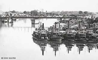 Then: A variety of cargo boats pause for a shot taken in 1904 on the Sacramento River waterfront with the M Street Bridge in the background. This bridge was later replaced.