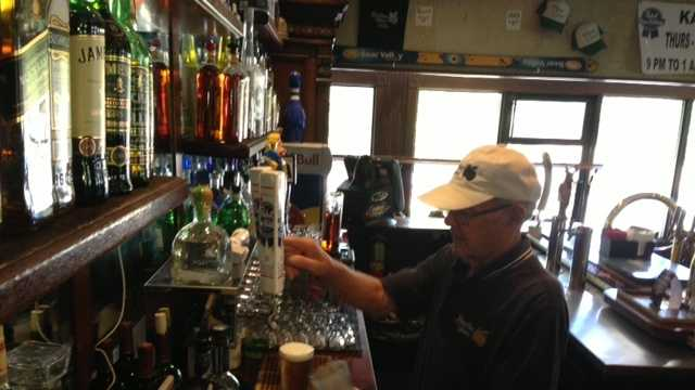 Bobby Moon pours a beer from behind the bar inside Sacramento's Pine Cove bar.