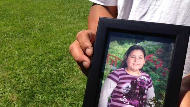 A family member holds a photograph of a slain 10-year old girl.