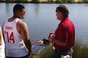 Junior team leader Andre Torres talks with a race official just after the juniors placed their boat in the water.