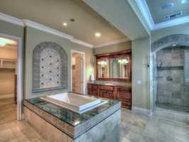 Here's a spa-like tub with vanishing edge inside the master bathroom.