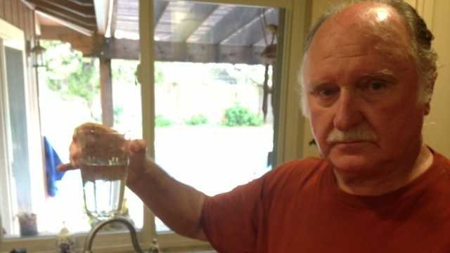 Vern Burrows holds up a glass of tap water inside the kitchen of an El Margarita neighborhood home.