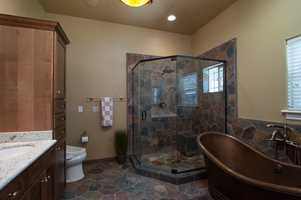 The master bath features this stone shower, a copper tub and dual sinks.