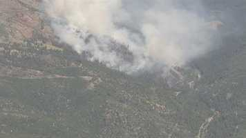 Fire crews battle a grass fire in the El Dorado National Forest on Monday.