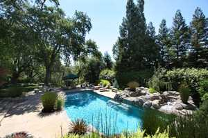 Both the river and this pool are within arm's reach at this home.