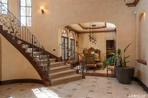 A grand staircase extends out next to the dining area.