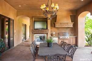 The backyard patio is complete with a fireplace, television, sink and cooler.