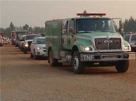 A caravan of fire equipment heads back out to the fire lines for the day shift.