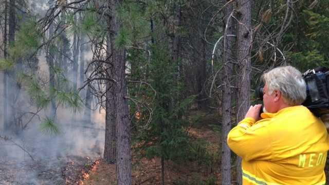 Reporter Melinda Meza snaps a photo of her photographer, who shoots the flames near Yosemite.