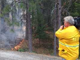 Reporter Melinda Meza snaps a photo of her photographer, who shoots the flames near Yosemite.