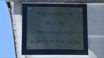 "A sign hanging off the front of the house jokingly warns that ""Trespasser will be drugged and buried in the yard."""