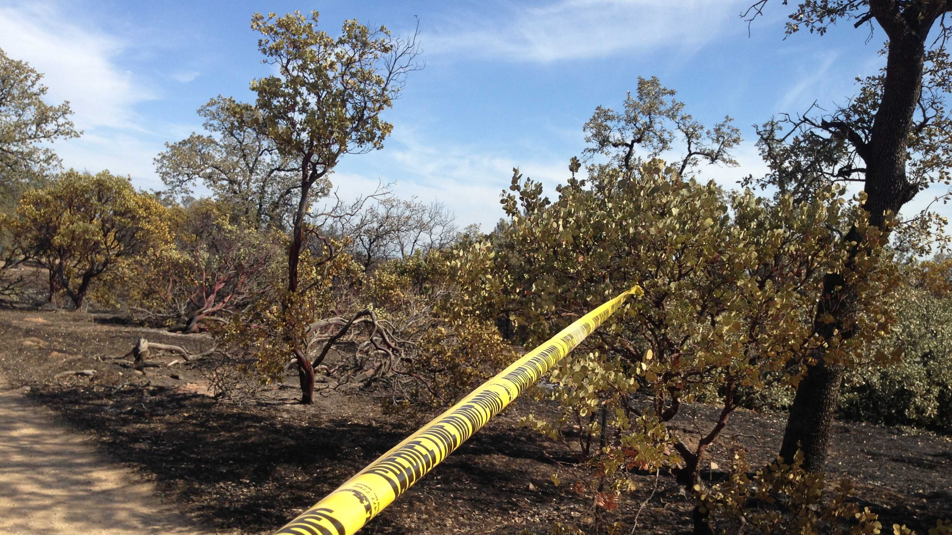 Crime tape marks the spot where a man's burned body was discovered in Shasta County.