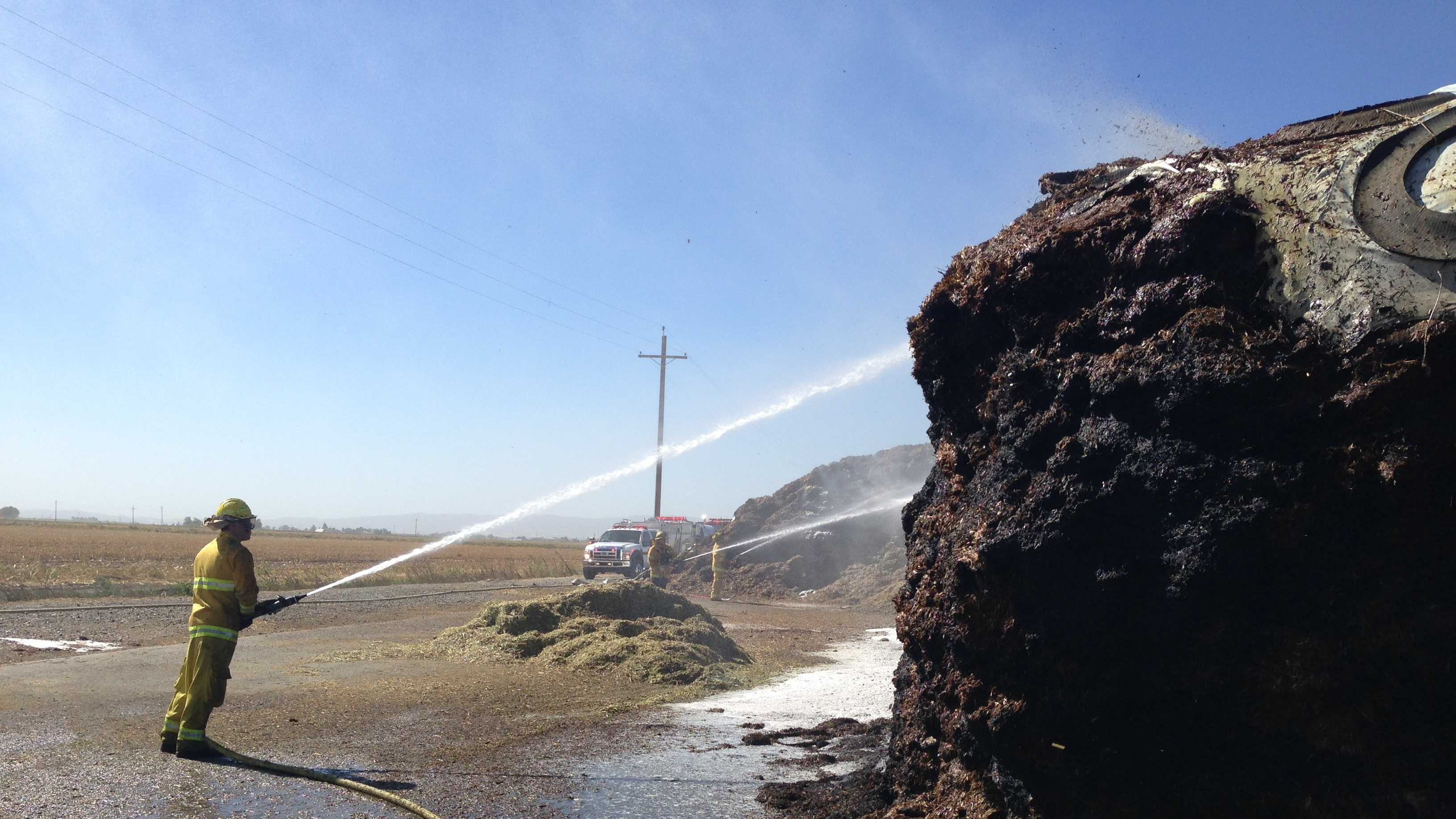 Firefighters douse a hay fire near Dixon.