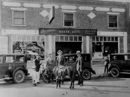 The Mahan family stands in front of its automobile dealership in 1926. The horse in the picture was part of a trade-in for a more modern mode of transportation.