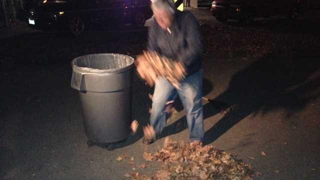 Ray Wagner picks up leaves he raked Friday morning.