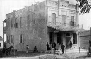 In this photo, patrons stand outside the Hasman's building during the first part of the century. An 1890s fire all but destroyed the entire building, which was later constructed with brick and metal shutters to protect it from any future fires.