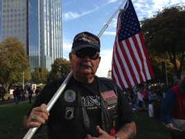 Doug Powers, who says he served during the Cuban Missile Crisis, carries a large flag at the parade (Nov. 11, 2013).
