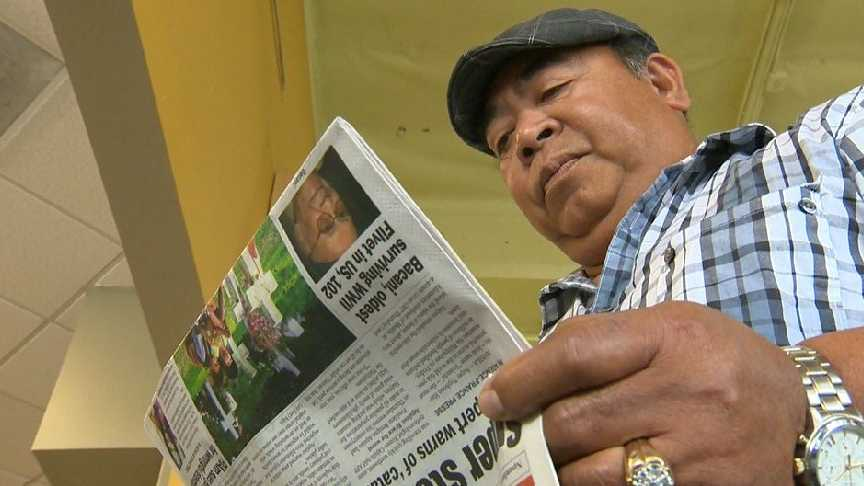 Rick Pasalo of Sacramento reads a Filipino-American newspaper for information about Typhoon Haiyan.