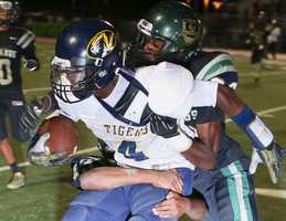 #8 - Inderkum's Larry Hardy tries to get away as two Monterey Trail players tackle him.