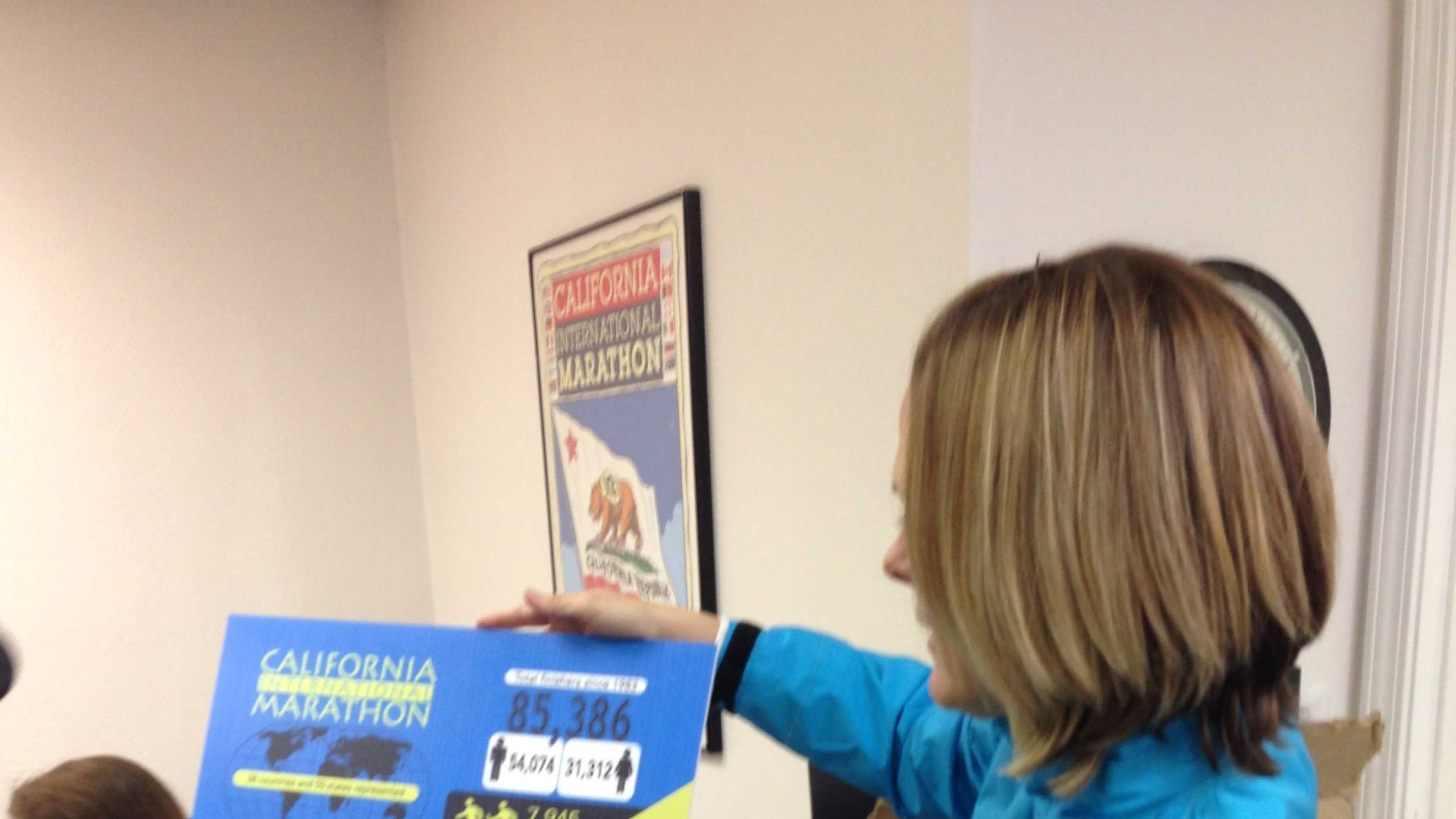 Sacramento Running Association Director Ellen Moore shows a flowchart of stats for the CIM at the association's office.
